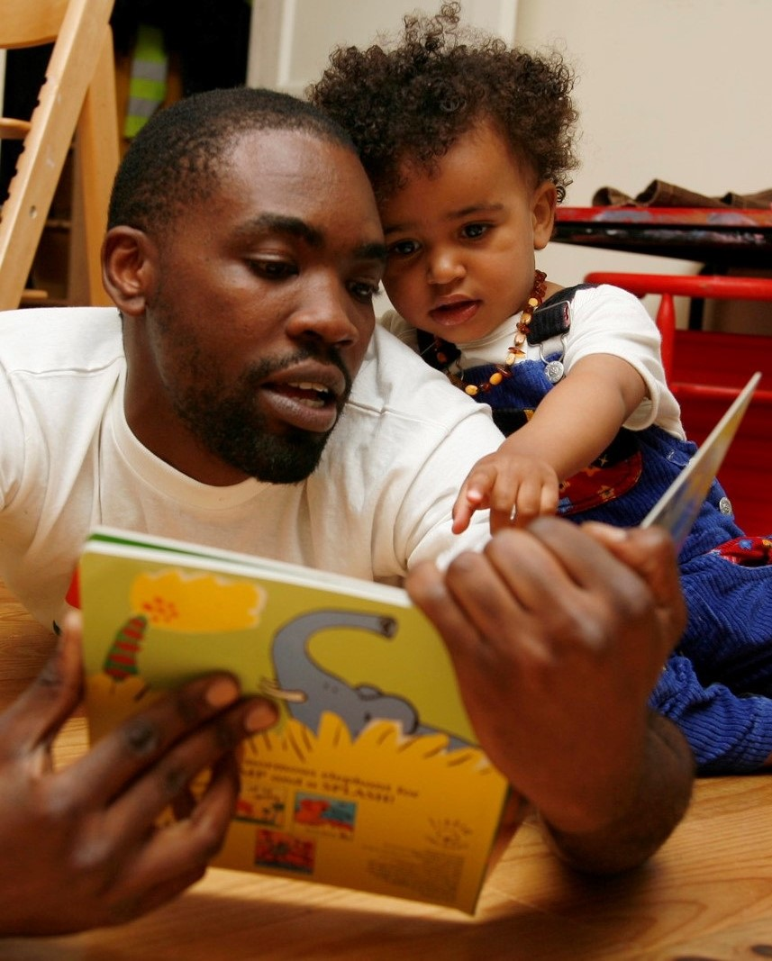 Father reading to his young daughter